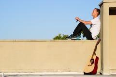 Musicien assis dehors avec une guitare acoustique Images stock