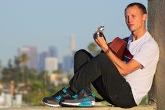 Musicien assis jouant la guitare avec de la LA à l'arrière-plan Photos stock