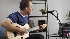 Musicien chantant et jouant la guitare électrique dans le studio à la maison de musique clips vidéos
