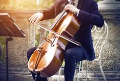 Musicien dans un costume se reposant sur une chaise blanche et jouant sur le violoncelle image stock