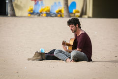 Musicien de rue avec une guitare se reposant à la plage sablonneuse de l'île de Ténérife, Espagne Photo libre de droits