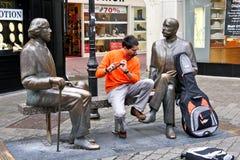 Musicien de rue s'asseyant sur un banc entre Oscar Wilde et Eduard Vilde, Galway, Irlande image libre de droits
