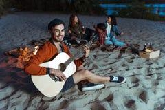 Musicien de sourire jouant la guitare tandis que ses amis s'asseyant derrière sur la plage sablonneuse Images libres de droits