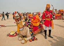 Musicien en forme vive avec le saxophone rêvant près de son chameau Image stock