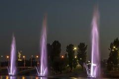 Musicien et les fontaines d'éclairage à la ville de nuit photographie stock libre de droits