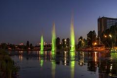 Musicien et les fontaines d'éclairage à la ville de nuit images stock