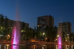 Musicien et les fontaines d'éclairage à la ville de nuit photographie stock