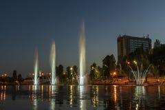 Musicien et les fontaines d'éclairage à la ville de nuit photo libre de droits