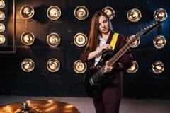 Musicien féminin dans le costume jouant sur la guitare électrique Images libres de droits