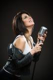 Musicien féminin de roche tenant la MIC Photos stock