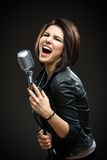 Musicien féminin de roche tenant le microphone Image stock