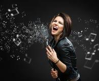 Musicien féminin de roche tenant retentir le microphone avec la mélodie dans le ciel Image stock