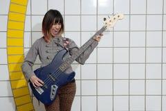 Musicien féminin jouant la guitare dans le souterrain avec la langue  Photographie stock