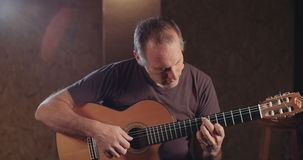 Musicien jouant la guitare acoustique dans un studio d'enregistrement banque de vidéos