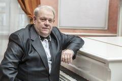 Musicien mûr jouant un piano blanc Images stock