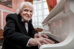Musicien mûr jouant un piano blanc Photographie stock libre de droits