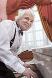 Musicien mûr jouant un piano blanc Image stock