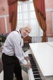 Musicien mûr jouant un piano blanc Photos libres de droits