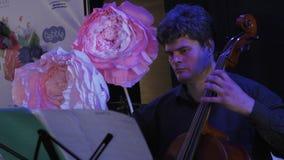 Musicista adulto che gioca sul contrabbasso sull'evento di celebrazione in ristorante concerto video d archivio