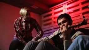 Musicista alla moda che gioca chitarra acustica in garage archivi video