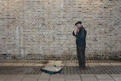 Musicista ambulante classico che sta contro un muro di mattoni Immagini Stock Libere da Diritti