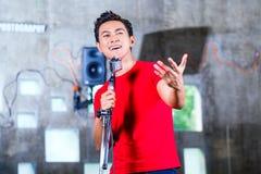Musicista asiatico producendo canzone in studio di registrazione Immagini Stock