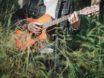 Musicista bello che gioca chitarra acustica ai precedenti della sfuocatura del campo di erba Giorno di musica del mondo musica e  immagine stock