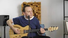 Musicista che gioca chitarra elettrica nello studio domestico di musica video d archivio