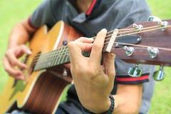 Musicista che gioca chitarra nel parco fotografie stock