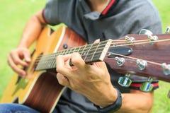 Musicista che gioca chitarra nel parco fotografie stock libere da diritti
