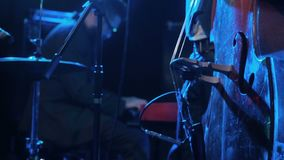 Musicista che gioca contrabbasso con il pianista sul primo piano del fondo Buio di legno del contrabbasso del gioco dell'artista  archivi video