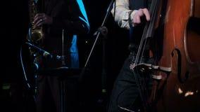 Musicista che gioca contrabbasso con il sassofonista sul primo piano del fondo Buio di legno del contrabbasso del gioco dell'arti stock footage
