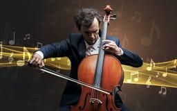 Musicista che gioca sul violoncello con le note intorno fotografia stock