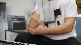 Musicista che ha dolore del polso mentre giocando la tastiera del Midi nello studio domestico di musica stock footage