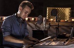 Musicista che lavora e che produce musica nel suo studio sano moderno Fotografia Stock