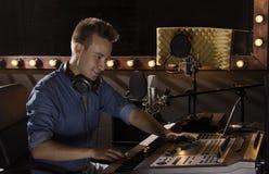 Musicista che lavora e che produce musica nel suo studio sano moderno Immagine Stock