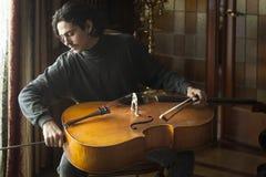 Musicista che prepara violoncello per essere giocato fotografia stock libera da diritti