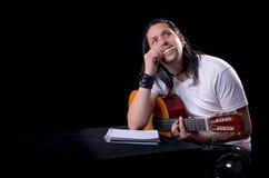 Musicista del chitarrista che scrive una canzone sulla sua chitarra Immagine Stock