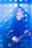 Musicista della roccia dei giovani che gioca chitarra elettrica e che canta Rock star su fondo dei riflettori Fotografie Stock Libere da Diritti