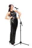 Musicista femminile che firma su un microfono Fotografia Stock