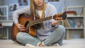 Musicista femminile che sintonizza la chitarra sul sofà domestico, godendo della melodia, praticante stock footage