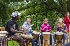 Musicista nero dai demostrates dell'Africa come giocare i tamburi a Fotografia Stock Libera da Diritti