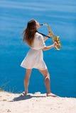 Musicista sulla spiaggia rocciosa Fotografie Stock
