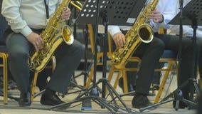 Musicisti che giocano i sassofoni nella fase, primo piano 4k video d archivio