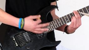 Musicus die een zwarte elektrische gitaar spelen stock footage
