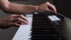 Musicus die het toetsenbord van MIDI/het controlemechanismesynthesizer van MIDI in studio spelen stock videobeelden
