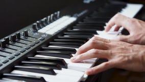 Musicus die het toetsenbord van MIDI/het controlemechanismesynthesizer van MIDI in studio spelen stock footage