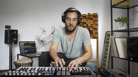 Musicus die het toetsenbord van Midi in de studio van de huismuziek spelen stock video