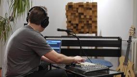 Musicus die het toetsenbord van Midi in de studio van de huismuziek spelen stock videobeelden