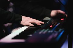 Musicus het spelen op de de pianosleutels van de toetsenbordsynthesizer De musicus speelt een muzikaal instrument op het overlegs royalty-vrije stock foto's